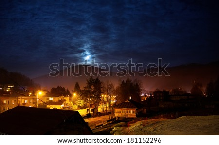 moon on the old town in the mountains at the twilight