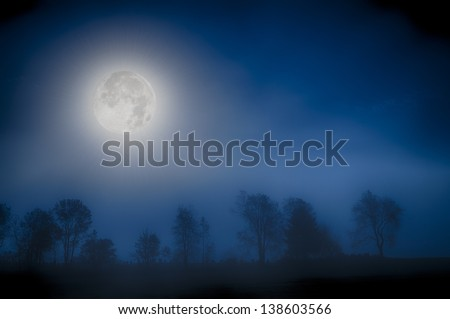 Moon over a foggy treeline, Stowe, Vermont, USA - stock photo