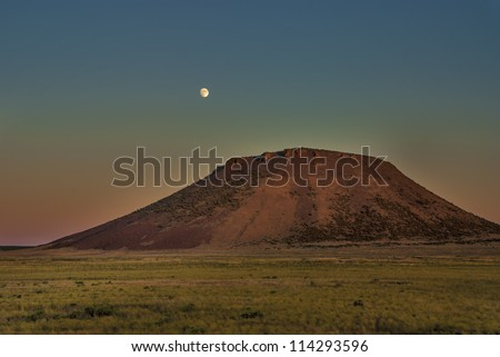 Moon rises over a southern Idaho butte at sunset