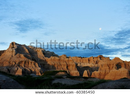 Moon rises over the mountains at Badlands - stock photo