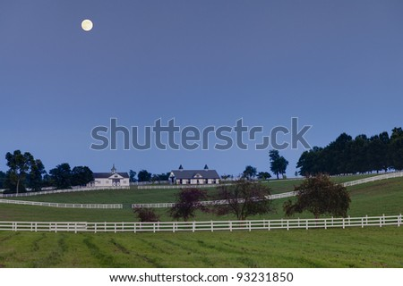 Moon rising over a horse farm - stock photo