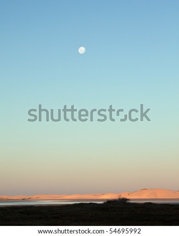 Moon rising over a lagoon in the late afternoon - stock photo
