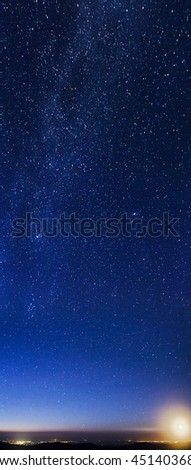 Moon rising over mountains and city lights with northern part of milky way galaxy