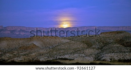 Moon rising over the Sierra del Carmen Mountains, Mexico. Seen from banks of the Rio Grande river in Big Bend National Park, Texas, United States. - stock photo