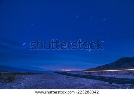 Moonlit road with car's headlight trails and star-trails in Death Valley, California