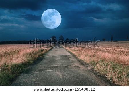 Moonrise over asphalt road - stock photo