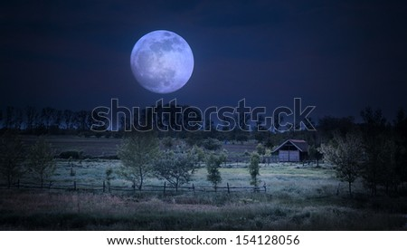 Moonrise over farm - stock photo