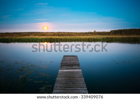 Moonrise over river lake pond in summer evening. Wooden boards pier on Calm Water Of Lake, River - stock photo