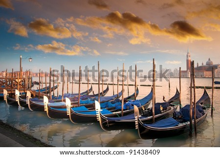 Moored gondolas in a row in evening light in Venice, Italy - stock photo
