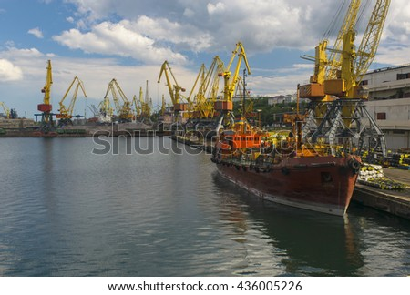 Moored vessel on the pier with seaport cranes and cargo background