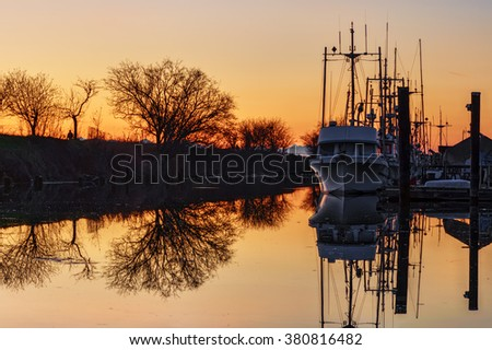 Moored yachts in river, during sunset - stock photo