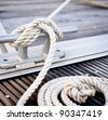 Mooring rope/ White mooring rope tied around steel anchor on boat or ship - stock photo
