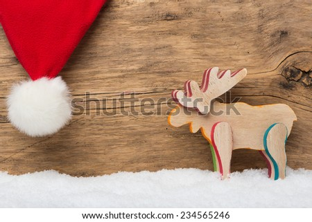 Moose and santa hat on wooden background with snow