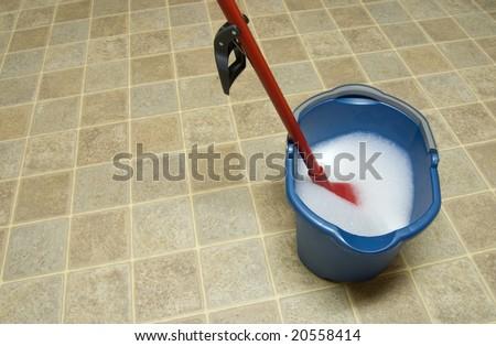 Mop and mop bucket on linoleum floor - stock photo