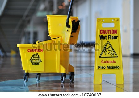 Mop bucket and caution sign - stock photo