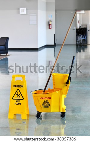 Mop bucket and caution sign on a web floor - stock photo