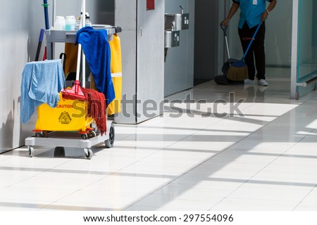 Mop bucket on cleaning in process and worker background - stock photo