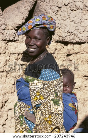MOPTI, MALI - SEPTEMBER 17, 2009: Local Fulani woman carries her child on September 17, 2009 in Mopti, Mali. Fula people are the largest migratory ethnic group in the world - stock photo
