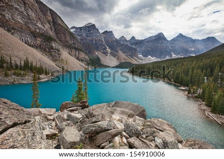 Moraine lake in the rocky mountains on a cloudy day - stock photo