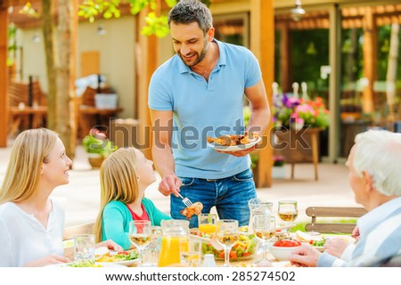 More chicken? Happy family of five people communicating and enjoying meal together while sitting at the dining table in formal garden - stock photo