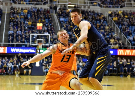 MORGANTOWN, WV - MARCH 7: OSU guard Phil Forte III (13) battles to get open as WVU forward Nathan Adrian (11) defends in the Big 12 Conference college basketball game March 7, 2015 in Morgantown, WV.  - stock photo