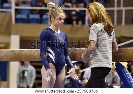 MORGANTOWN, WV - MARCH 8: Penn State female gymnast Emma Sibson receives last minute instruction from a coach prior to performing on beam during a dual meet March 8, 2015 in Morgantown, WV.  - stock photo