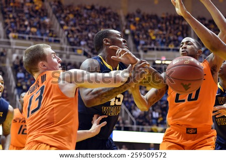 MORGANTOWN, WV - MARCH 7: WVU forward Elijah Macon (45) loses control of the ball as his arm is hit by a defender during the Big 12 Conference college basketball game March 7, 2015 in Morgantown, WV.  - stock photo