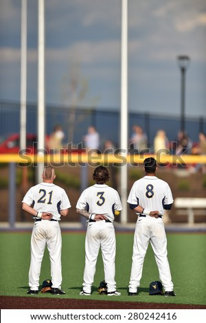 MORGANTOWN, WV - MAY 1: Three WVU baseball players stand together during the National Anthem prior to a Big 12 conference baseball game May 1, 2015 in Morgantown, WV.  - stock photo