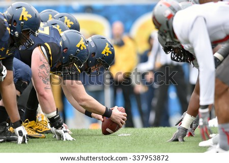 MORGANTOWN, WV - NOVEMBER 7: The WVU offensive line lines up over the ball during the football game November 7, 2015 in Morgantown, WV. - stock photo