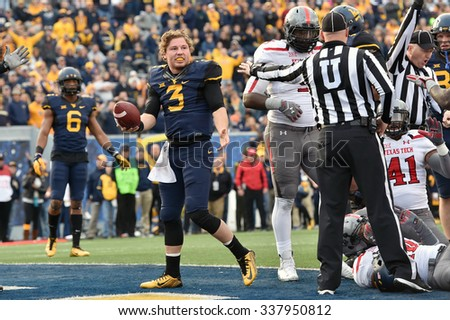 MORGANTOWN, WV - NOVEMBER 7: West Virginia Mountaineers quarterback Skyler Howard (3) emerges from a pile in the end zone without his helmet during the football game November 7, 2015 in Morgantown, WV - stock photo