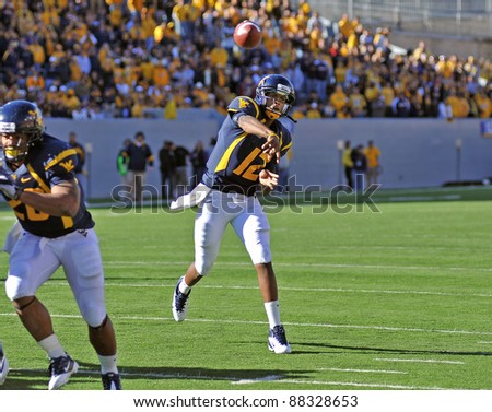 MORGANTOWN, WV - NOVEMBER 5: WVU quarterback Geno Smith (#12) throws a pass near the endzone in a football game against Louisville November 5, 2011 in Morgantown, WV. - stock photo