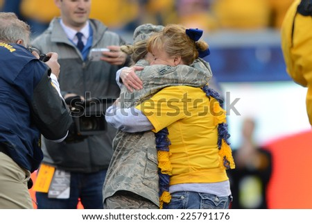 MORGANTOWN, WV - OCTOBER 4: A family is reunited with their daughter, who has been deployed overseas, during the homecoming football game October 4, 2014 in Morgantown, WV.  - stock photo