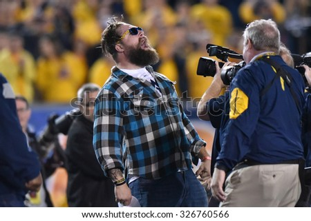 MORGANTOWN, WV - OCTOBER 10: Former WVU and NFL fullback Owen Schmitt yells as he enters the field on homecoming during the Big 12 football game October 10, 2015 in Morgantown, WV.  - stock photo