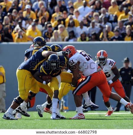 MORGANTOWN, WV - OCTOBER 23: Syracuse University defensive tackle Andrew Lewis (#51) lifts the leg of WVU quarterback Geno Smith for a sack in a Big East game October 23, 2010 in Morgantown, WV. - stock photo