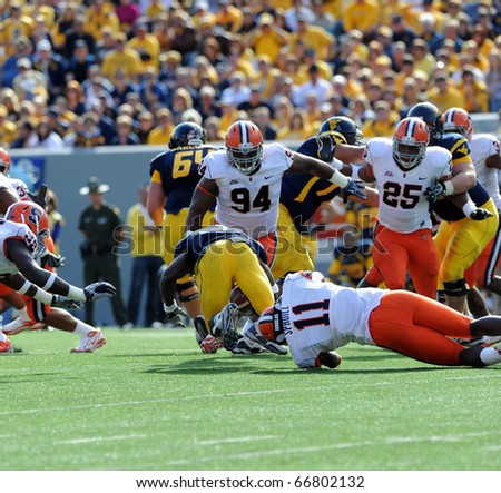 MORGANTOWN, WV - OCTOBER 23: Syracuse University linebacker Marquis Spruill (#11) drags down a WVU ball carrier in a Big East game October 23, 2010 in Morgantown, WV. - stock photo