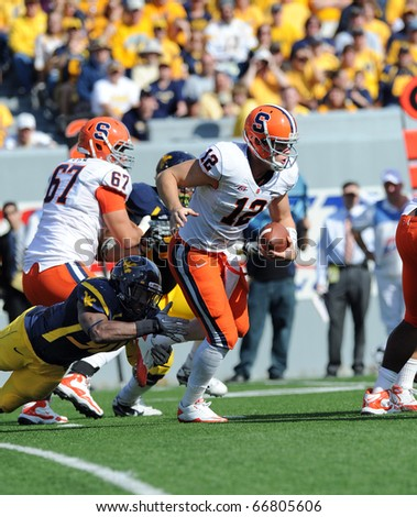 MORGANTOWN, WV - OCTOBER 23: Syracuse University quarterback Ryan Nassib (#12) tries to elude WVU linebacker J.T. Thomas (diving, left) on a pass play October 23, 2010 in Morgantown, WV. - stock photo