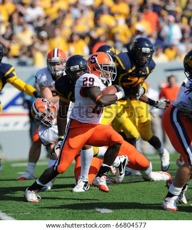 MORGANTOWN, WV - OCTOBER 23: Syracuse University running back Antwon Bailey (#29) runs with the ball behind a wall of blockers in a Big East game October 23, 2010 in Morgantown, WV. - stock photo