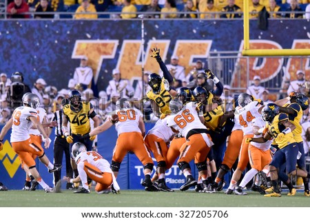MORGANTOWN, WV - OCTOBER 10:  WVU players try to block an extra point from Oklahoma State Cowboys place kicker Ben Grogan (19) during the Big 12 football game October 10, 2015 in Morgantown, WV.  - stock photo