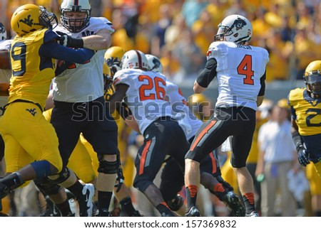 MORGANTOWN, WV - SEPTEMBER 28: Oklahoma State quarterback J.W. Walsh (4) stands in the pocket looking for a receiver during the football game September 28, 2013 in Morgantown, WV. - stock photo