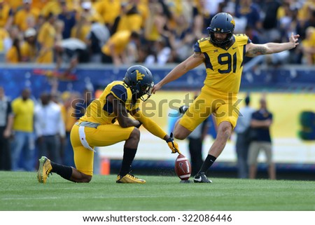 MORGANTOWN, WV - SEPTEMBER 26: West Virginia Mountaineers punter Nick O'Toole (91) boots the opening kickoff during the NCAA football game September 26, 2015 in Morgantown, WV.  - stock photo