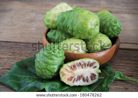 Morinda citrifolia or noni on wooden - stock photo