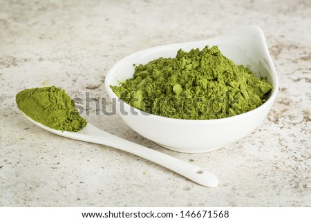 moringa leaf powder in a small bowl with a spoon against a ceramic tile background
