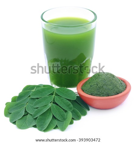 Moringa leaves with extract in a glass over white background - stock photo