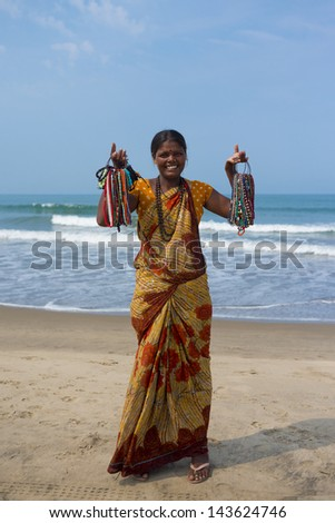 MORJIM, GOA, INDIA - MARCH 11: Indian women in traditional dress sells souvenirs on the beach, Morjim, March 11, 2013 in Goa India. This activity will provide a income stream on this Indian state