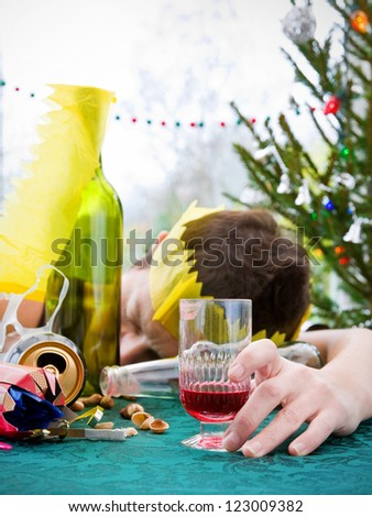 morning after christmas day, woman asleep on table with alcohol at christmas - stock photo