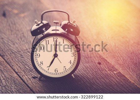 Morning alarm clock on table. Vintage filter. - stock photo