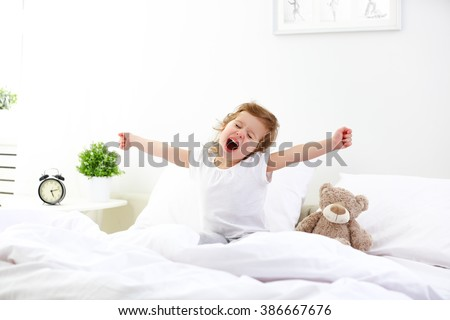 morning awakening little child girl in bed - stock photo
