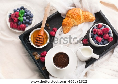 Morning breakfast in bed with cup of coffee, croissants, fresh berries and honey on wooden tray, top view
