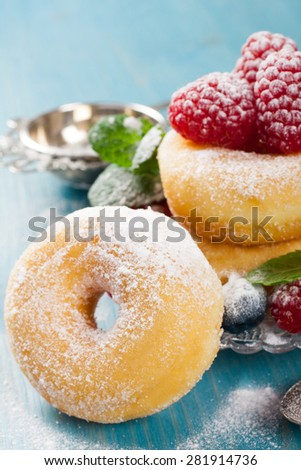 Morning breakfast with mini donuts and berries on plate under powdered sugar on blue wooden background.  Tasty donuts closeup. Doughnut.  - stock photo