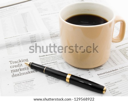 Morning coffee and pen on a morning paper business news - stock photo